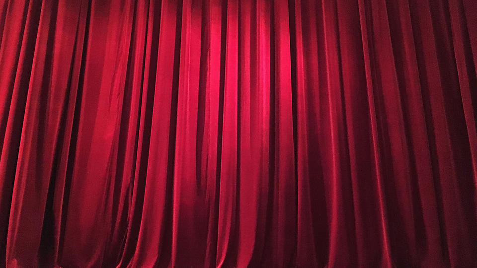 Theatre curtain closed on stage.