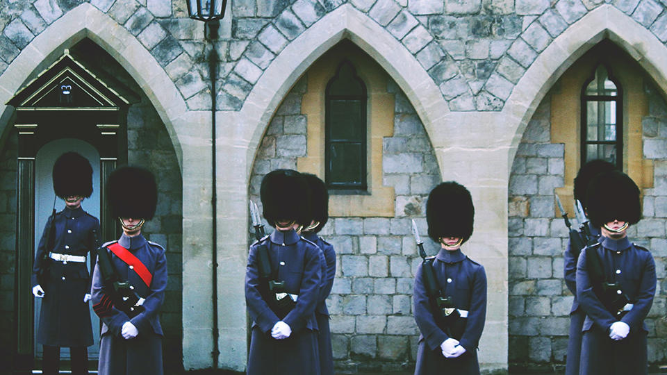Guards standing outside of a stone building