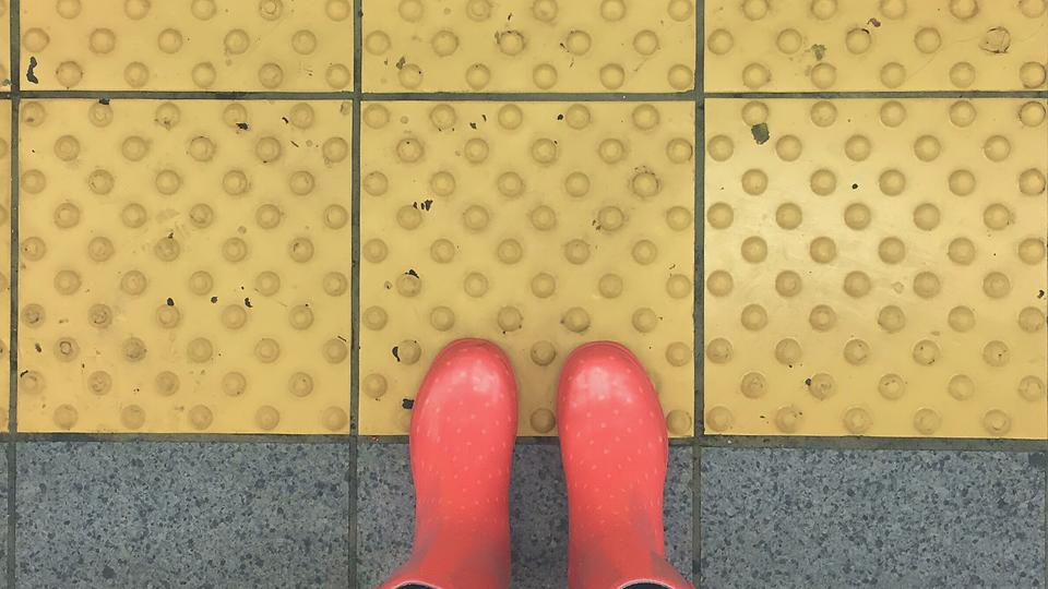 Red rain boots at a crosswalk