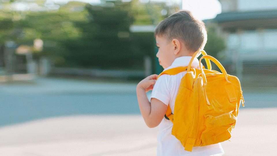 Young boy with a yellow backpack waiting for a bus.