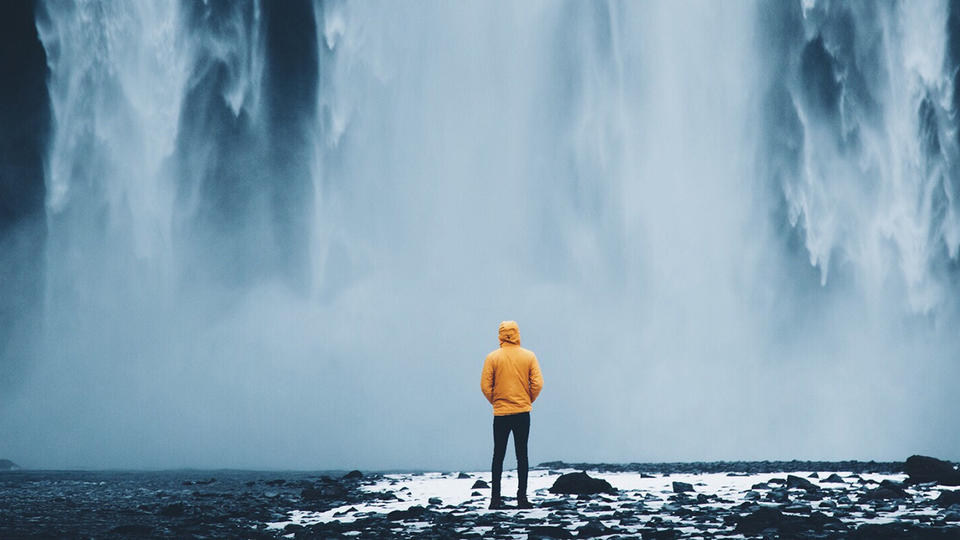 Person standing at the bottom of a waterfall