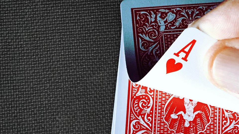 Flipping over a playing card to reveal the ace of hearts
