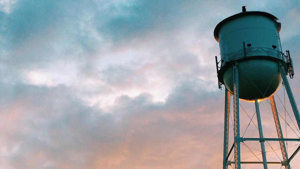 Water tower with sunset behind it.