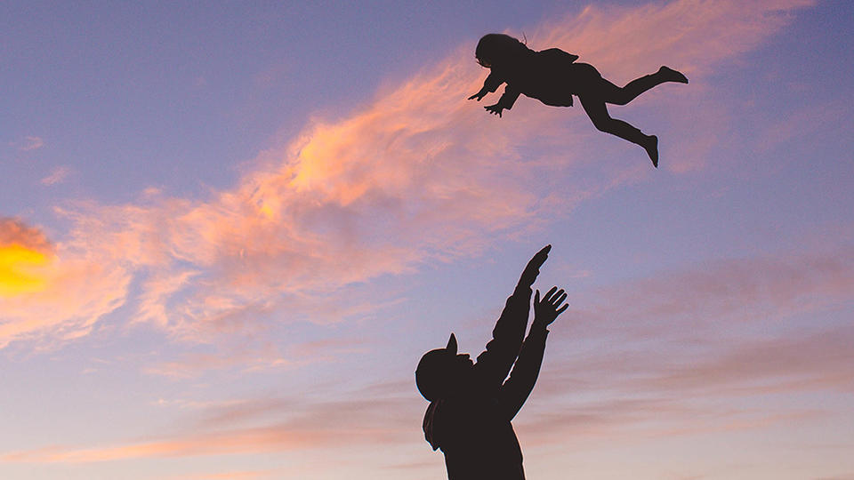 Person throwing a toddler up in the air