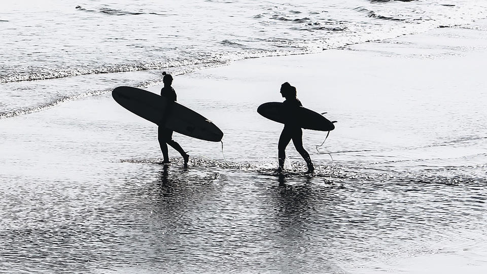 Two women going out to surf