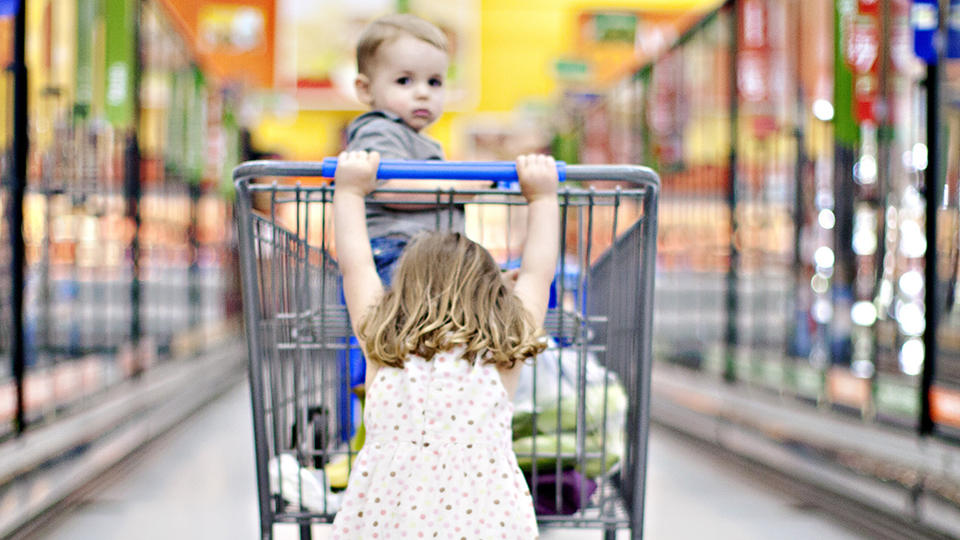 Little girl pushing younger sibling in a grocery cart.
