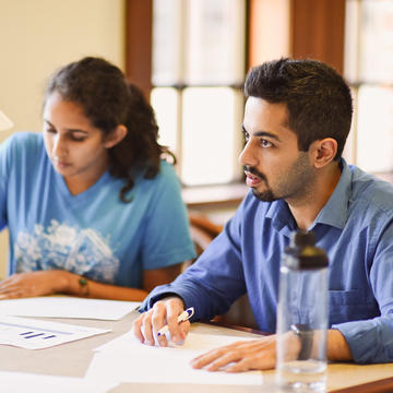 Male student in blue shirt working with female student in blue shirt at a table