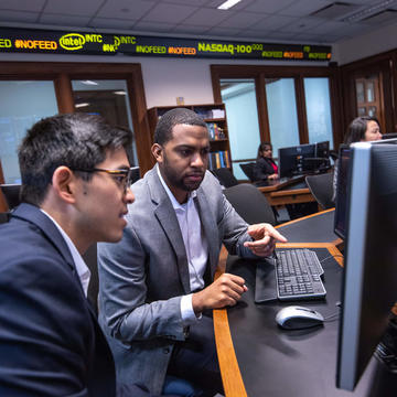Two students in the Finance Center looking at a monitor