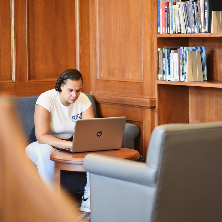 Female student in white Rice Business t-shirt working on laptop in the library